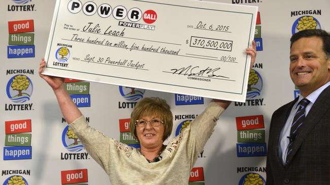 Pictures like this one of the winner of October's Powerball jackpot, make us imagine it could be us up there holding the novelty cheque. Picture: Dale G. Young/The Detroit News via AP