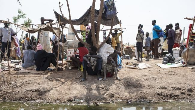People go about their daily lives alongside dirty water in a camp for displaced people, l