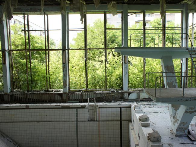 Empty swimming pools sit in derelict buildings. Picture: super — collider.