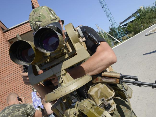 Watchful ... a Ukrainian border guard looks through binoculars at the checkpoint with Russia. Picture: Alexander Khudoteply