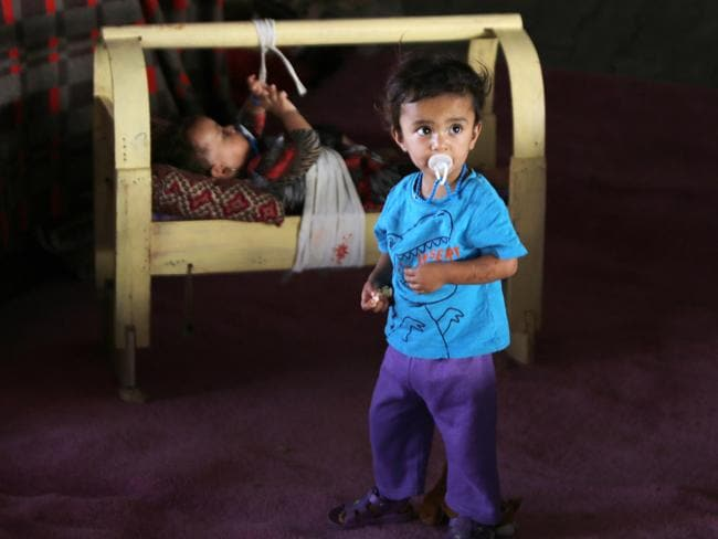 Innocent victims ... an Iraqi Yazidi boy stands near a baby under a bridge where displaced people of this religious minority found refuge after Islamic State militants attacked the town of Sinjar on August 17.