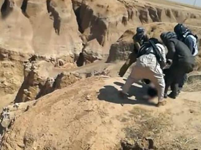 Into the abyss ... jihadists drag bodies into Syria's al-Raqqa desert for disposal in this gorge.