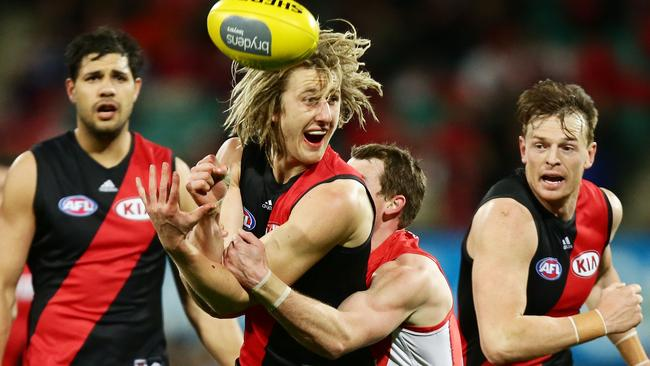 Dyson Heppell gets his handball away as he is tackled.