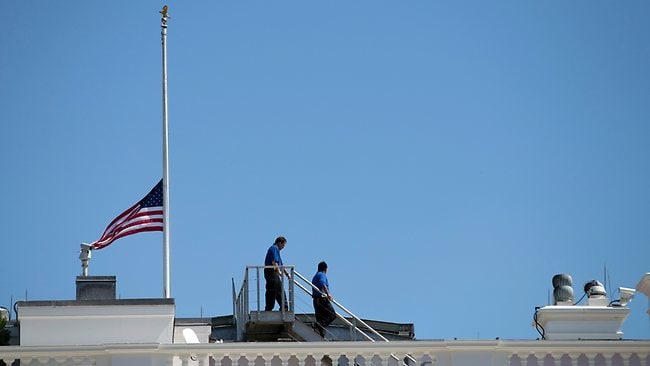 White House workers walk on the roof of the White House after lowering the flag to half staff for the death of US ambassador to Libya Christopher Stevens.