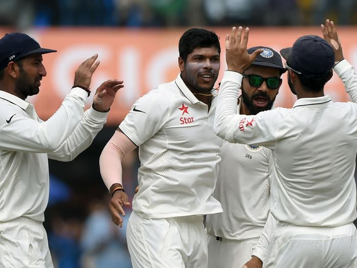 Umesh Yadav (C) celebrates with teammates after taking the wicket of Tom Latham.