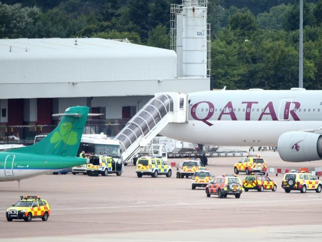 Swarm...The Qatar Airways flight from Doha sits on the tarmac after having a military escort into Manchester Airport. Picture: Getty