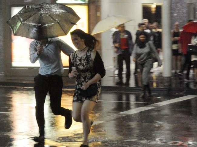 A couple make a break for it as more rain lashed the city early this morning: Gordon McComiskie