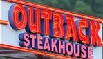 """Huntsville, Alabama, USA - June 9, 2011: Outback Steakhouse sign illuminated in the early evening. Sign located on Whitesburg Drive in Huntsville, Alabama."""