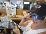 Carol Jensen at the Black Bear Diner displays a hat and eclipse glasses August 19, 2017 in Madras, Oregon. The diner is selling merchandise for the August 21 total solar eclipse that will be visible across the continental US. / AFP PHOTO / STAN HONDA