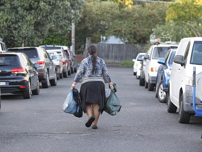 Elena Bobolas walks down the street removing rubbish from the property and taking it else