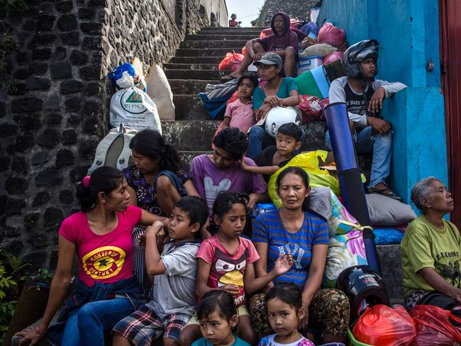 People gather as they wait their transport to a temporary shelter at Sibetan village in September in Bali after Mount Agung started rumbling. Picture: Getty