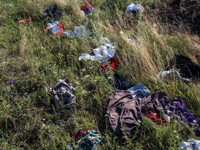 Chaos ... clothing belonging to travellers on Malaysia Airlines flight MH17 is strewn in the grass at the crash site. Picture: Brendan Hoffman