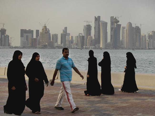 New high-rise buildings of Qatar's capital Doha in the background, Qatari women and a man enjoy walking by the sea. Picture: Kamran Jebreili/AP