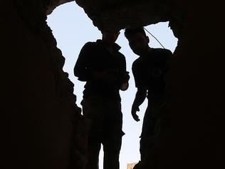 Iraqi forces are seen through a hole in the roof during their advance in the Old City of Mosul on June 25, 2017, during the ongoing offensive to retake the last district held by the Islamic State (IS) group. / AFP PHOTO / AHMAD AL-RUBAYE
