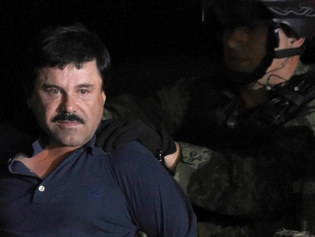 "Go directly to jail ... Drug kingpin Joaquin ""El Chapo"" Guzman is escorted into a helicopter at Mexico City's airport. Picture: AFP"