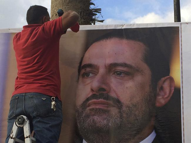 "Workers hang a poster of outgoing Prime Minister Saad Hariri with Arabic words that read, ""We are all Saad,"" on a seaside street in Beirut, Lebanon, Thursday, Nov. 9, 2017. Picture: AP."