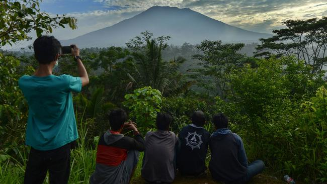People look at Mount Agung in Karangasem on the Indonesian resort island of Bali on September 24, 2017. Authorities have raised alert levels for a volcano on the Indonesian resort island of Bali after hundreds of small tremors stoked fears it could erupt for the first time in more than 50 years. / AFP PHOTO / SONNY TUMBELAKA