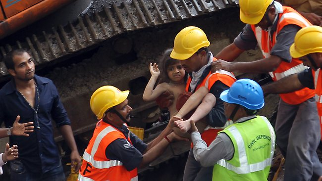 Rescue workers carry a girl from the rubble of an apartment building that collapsed in Mumbai. Picture: Rajanish Kakade