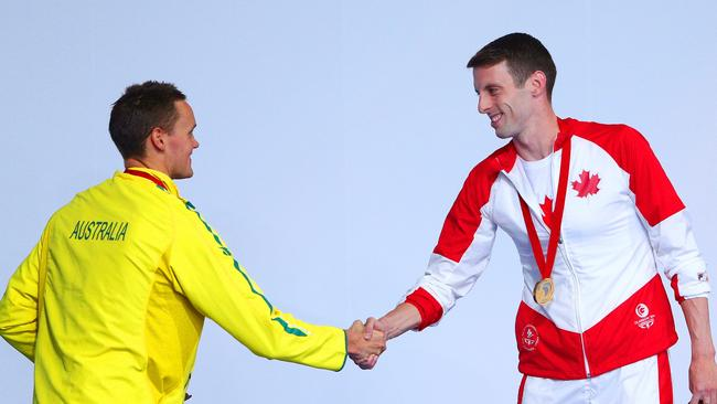 David McKeon puts his life at risk by sharing a handshake with Canadian swimmer Ryan Cochrane.