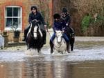 UNITED KINGDOM: People ride horses through flood water on the road leading to the village of Muchelney which has been cut off by flooding on January 6, 2014 near Langport in Somerset, England. Picture: Getty