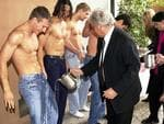 Harry Watt tips water over the jeans of a male model, prior to George Gross and Harry Watt fashion lunch in 2001.