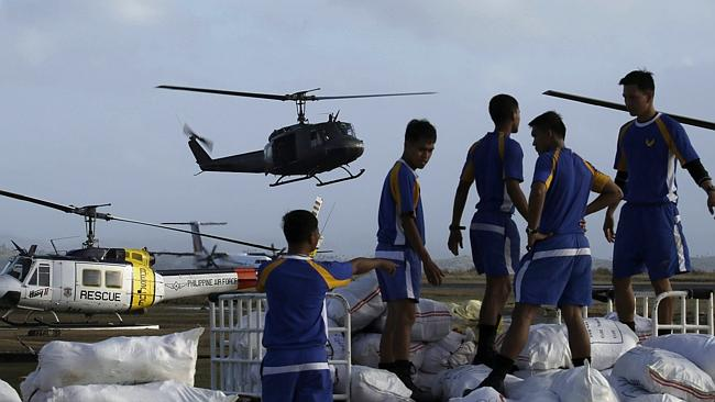 Soldiers prepare to load supplies into a Philippine air force helicopter at Tacloban airport. Picture: AP