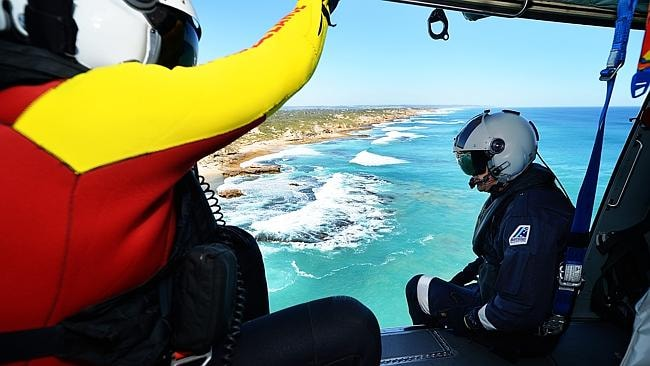 Air Crewman Andrew Keegan searches the sea above Blairgowrie from a helicopter. Picture: Tim Carrafa