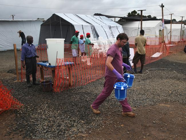 Medical emergency ... American virologist David Safronetz carries buckets containing blood samples from suspected Ebola patients to be tested at a newly-opened mobile laboratory for testing near Monrovia, Liberia. Picture: Getty