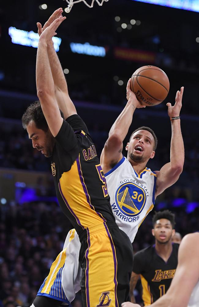 Golden State Warriors guard Stephen Curry, right, shoots vs the Los Angeles Lakers.
