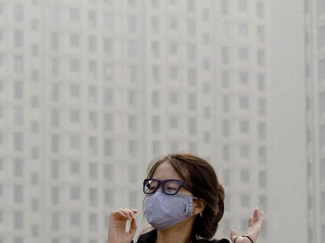 A woman looks after she puts on her mask near the residential apartment buildings shrouded by haze in Beijing.