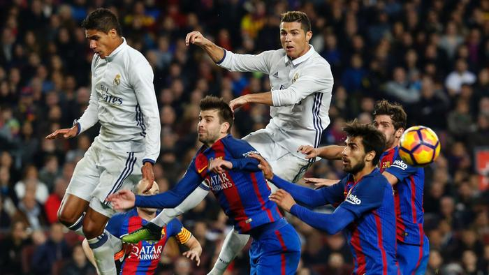 Real Madrid's French defender Raphael Varane (topL) heads the ball past Real Madrid's Portuguese forward Cristiano Ronaldo (topR) and Barcelona's defender Gerard Pique (C) during the Spanish league football match FC Barcelona vs Real Madrid CF at the Camp Nou stadium in Barcelona on December 3, 2016. / AFP PHOTO / PAU BARRENA