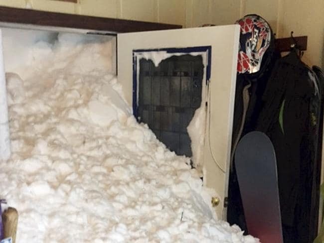 Snow bursts through Steven Siig's front door. Picture: Steven and Melissa Siig via AP