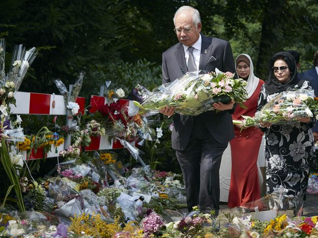 Honouring the victims ... Malaysian Prime Minister Najib Razak, and his wife Datin Sri Rosmah Mansor, right, lay flowers outside a military barracks where forensic experts are working to identify victmes. Picture: AP Photo/Phil Nijhuis