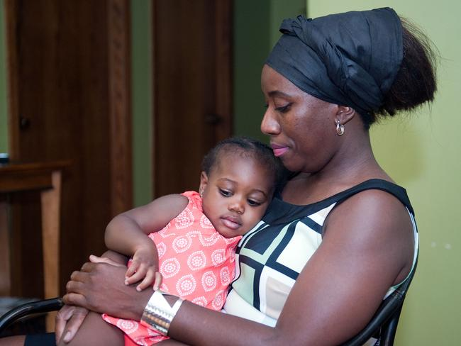 Grieving ... Decontee Sawyer, wife of Liberian government official Patrick Sawyer, a U.S. citizen who died from Ebola after travelling from Liberia to Nigeria, cradles her one-year-old daughter Bella at her home in Coon Rapids. Pic: Craig Lassig