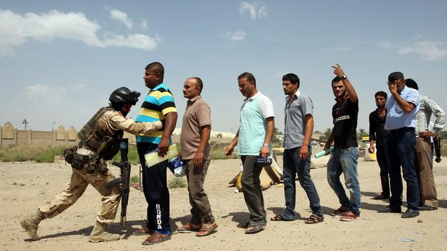An Iraqi soldier bodychecks men as they arrive to volunteer to join the fight against a major offensive by jihadists in northern Iraq. Picture: AFP/Ali Al-Saadi