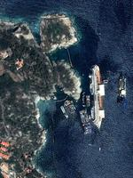 This photo provided by Astrium Tuesday, Sept.17, 2013 shows the capsized Costa Concordia on July 12, 2013. Engineers declared success on Tuesday, Sept.17, 2013 as the Costa Concordia cruise ship was pulled completely upright during an unprecedented 19-hour operation to wrench it from its side where it capsized last year off Tuscany. (AP Photo/CNES/Distribution Astrium Services/Spot Image)