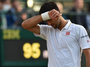 Serbia's Novak Djokovic reacts while playing US player Sam Querrey during their men's singles third round match on the fifth day of the 2016 Wimbledon Championships at The All England Lawn Tennis Club in Wimbledon, southwest London, on July 1, 2016. / AFP PHOTO / GLYN KIRK / RESTRICTED TO EDITORIAL USE