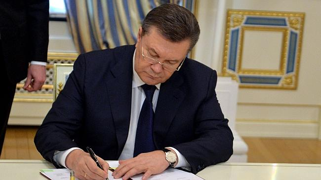Done deal ... Ukrainian President Viktor Yanukovych signs an agreement with the opposition to hold early elections and form a new unity government.
