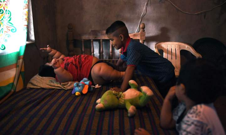 Ten-month-old Luis Gonzales (L) is pictured with his cousin Michel (C) and his brother Mario at his home in Tecoman, Colima state, Mexico on November 8, 2017. Luis Manuel Gonzales is almost like any ten-month-old baby; he babbles his first words and wants to touch everything, but he has a dramatic difference that puts his life at stake: he weighs 28 kilos. Luisito does not demand food constatly as it might be thinked, his case is part of the universe of childhood's obesity and diabetes that Mexico leads worldwide. / AFP PHOTO / PEDRO PARDO / TO GO WITH AFP STORY by JENNIFER GONZALEZ COVARRUBIAS