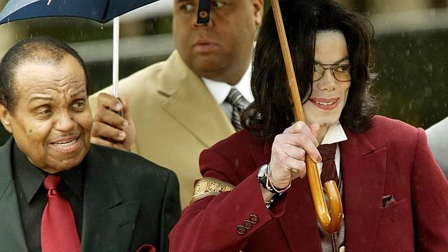 Singer Michael Jackson (R) leaves the Santa Barbara County Court after his child molestation trial with his father Joe (L) and bodyguards, Apr 27, 2005, in California. (AP PicRic/Francis)