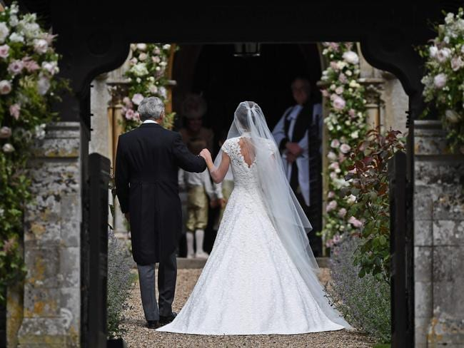 Here comes the bride ... Pippa walks into the church with her father.