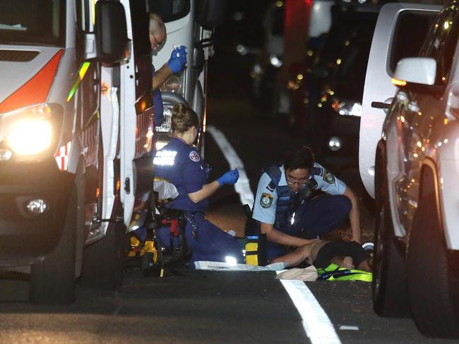 Police and paramedics treat the man after he was discovered lying in the middle of the road. Picture: Bill Hearne.