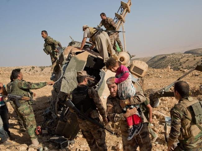 Passengers are helped out of the wreckage of an Iraqi military helicopters that crashed after delivering supplies to Yezidis still trapped in Iraq's Sinjar mountains. Picture: Adam Ferguson/The New York Times