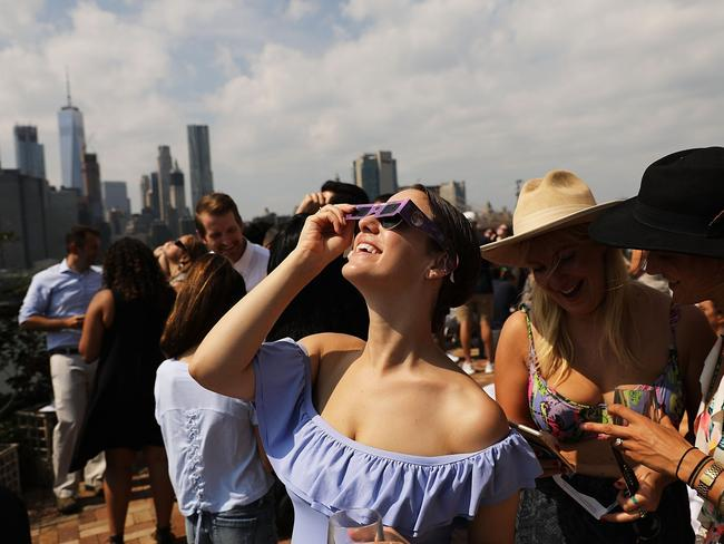 People watch a partial solar eclipse from the roof deck at the 1 Hotel Brooklyn Bridge in New York City. Picture: Spencer Platt/Getty Images/AFP