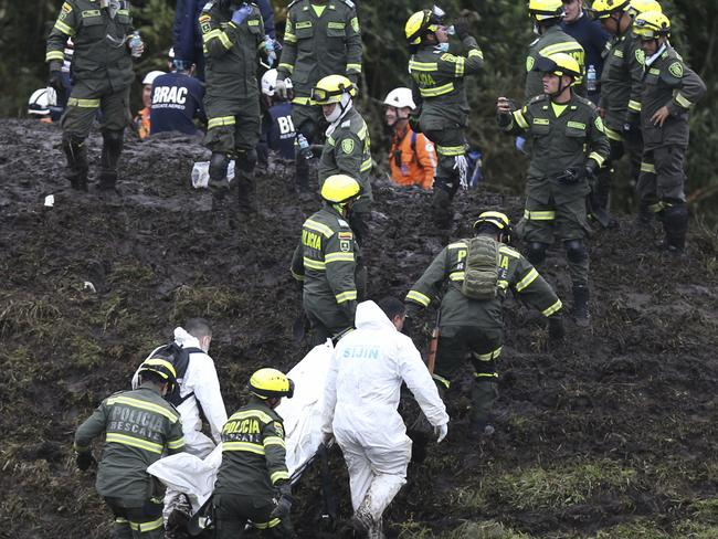 Rescue workers retrieve the body of one of the 76 victims, in the mountains near Medellin in Colombia.