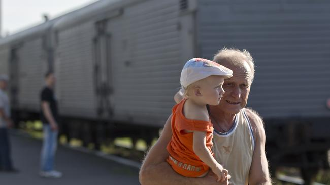 Locals beside the refrigerated train that is piling up with bodies from the MH17 crash site. Pic: News Corp
