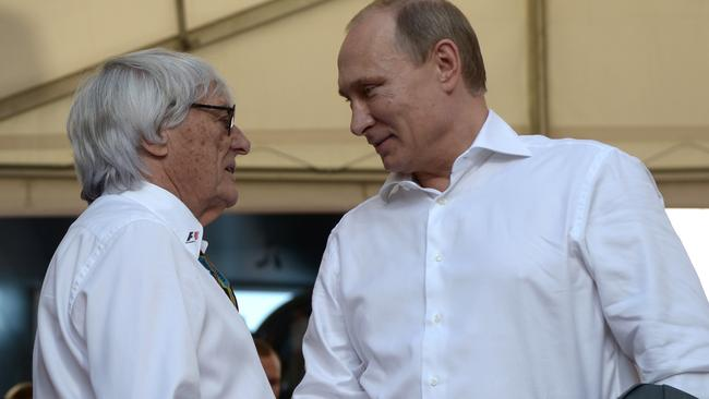Is Russian President Vladimir Putin, pictured here with Formula One chief executive Bernie Ecclestone, getting some practice in, in his shirt-front. Picture: AP Photo/RIA-Novosti, Alexei Nikolsky, Presidential Press Service
