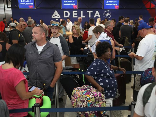 People stand in line as they wait for their flights at Terminal 2 where yesterday a shooter killed five people and wounded six others in the baggage area before he was taken into custody. Picture: Getty