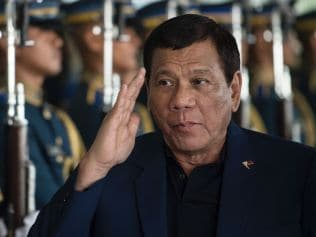 Philippine President Rodrigo Duterte walks past honour guards as he arrives at Manila international airport in Manila on May 24, 2017, after returning from a visit to Russia. Duterte threatened on May 24 to impose martial law nationwide to combat the rising threat of terrorism, after Islamist militants beheaded a policeman and took Catholic hostages while rampaging through a southern city. / AFP PHOTO / NOEL CELIS