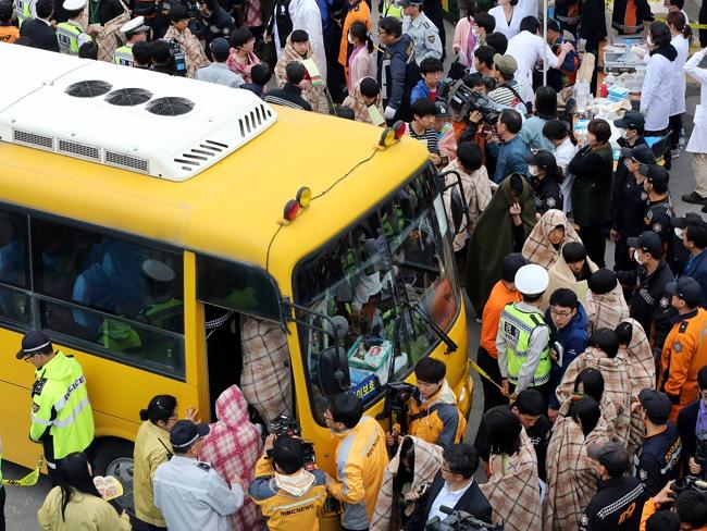 Moving to safety ... passengers wrapped in blankets being brought onto land in Jindo. Picture: Yonhap